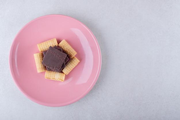 Rouleaux de gaufres et gaufrette enrobée de chocolat dans un plat, sur le marbre.