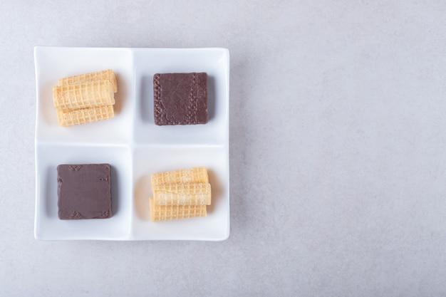 Rouleaux de gaufres et gaufrettes enrobées de chocolat dans un plat sur une table en marbre.