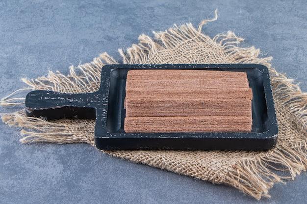 Rouleaux de gaufrettes au chocolat dans une planche sur une texture, sur fond de marbre.
