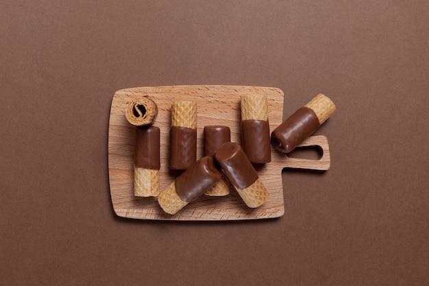 Rouleaux de gaufrettes croustillantes à moitié enrobés de chocolat au lait sur une planche à découper en bois, vue du dessus.