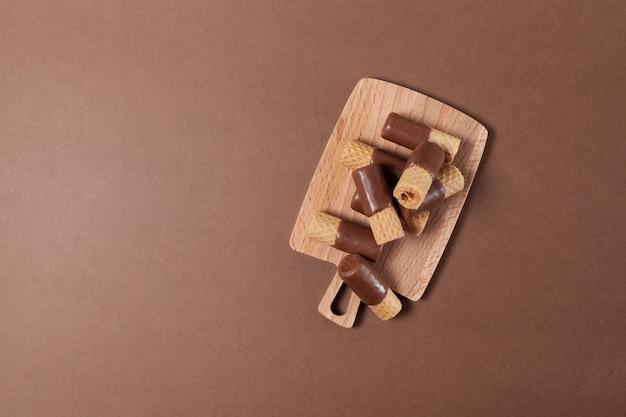 Rouleaux de gaufrettes croustillantes à moitié enrobés de chocolat au lait sur une planche de service en bois.