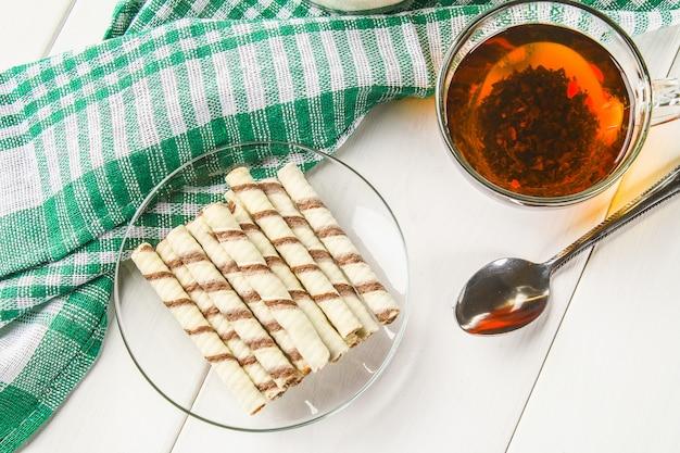 Rouleaux de gaufrettes à rayures, délicieux casse-croûte au chocolat sur une table en bois blanc.