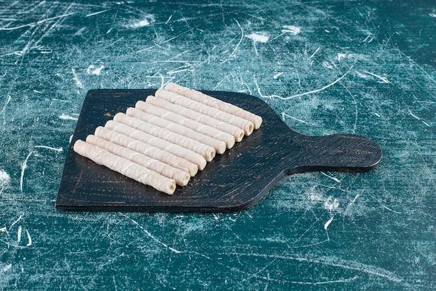 Rouleaux de gaufrettes savoureux sur une planche à découper noire.