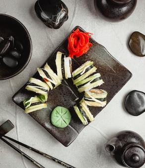 Rouleaux de gingembre et de wasabi sur un tableau noir.