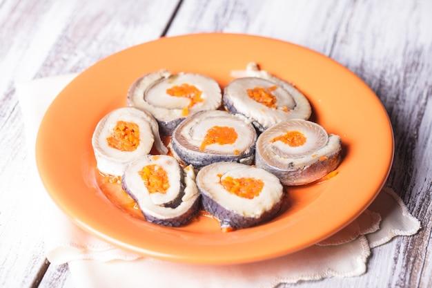 Rouleaux de hareng à la carotte sur plaque orange libre