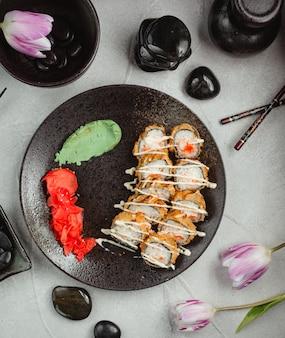 Rouleaux à l'intérieur d'une plaque noire avec du gingembre et du wasabi.