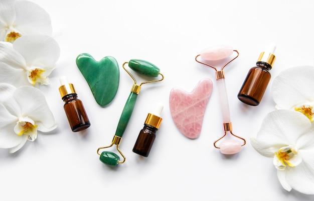 Rouleaux de jade de massage du visage sur mur blanc