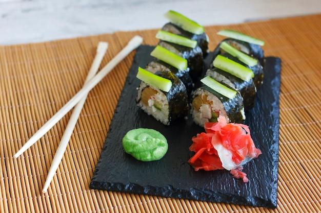Rouleaux japonais avec concombre, crabes et omelette sur un tableau noir avec wasabi et gingembre