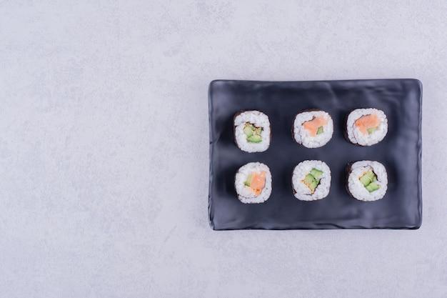 Rouleaux de maki au saké au saumon et à l'avocat dans un plateau en céramique noire