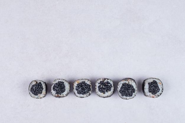 Rouleaux de maki décorés de caviar noir sur fond blanc.