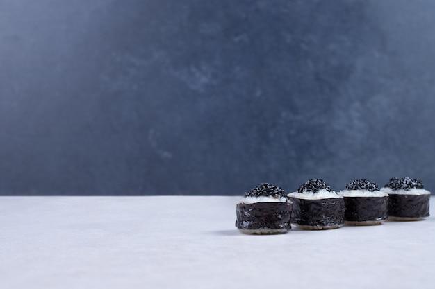 Rouleaux de maki décorés de caviar noir sur table blanche.