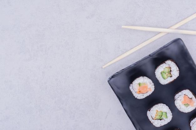 Rouleaux de maki saké dans un plateau en céramique noire