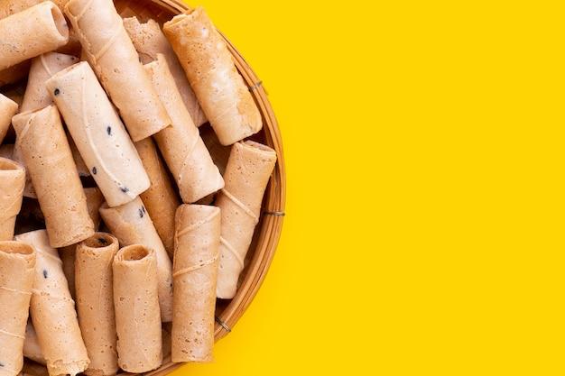 Rouleaux de noix de coco croustillants thaïlandais dans un panier en bambou sur fond jaune.