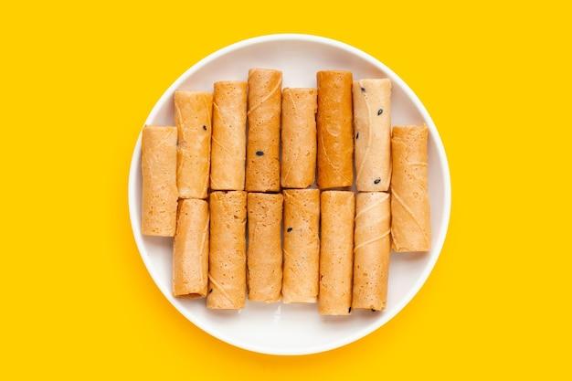 Rouleaux de noix de coco croustillants thaïlandais en plaque blanche sur fond jaune.