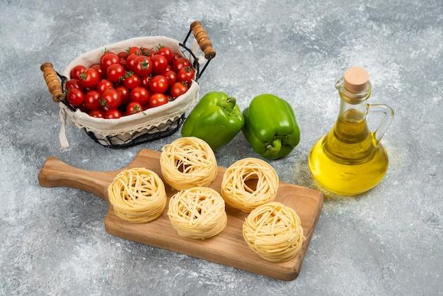 Rouleaux de nouilles au poivron vert, tomates cerises et huile d'olive.