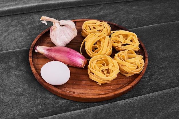 Rouleaux de nouilles avec des ingrédients sur un tableau noir en bois.