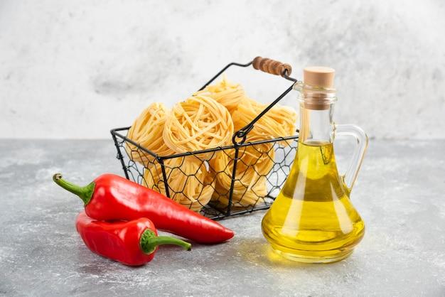 Rouleaux de nouilles servis avec de l'huile d'olive et des piments rouges.
