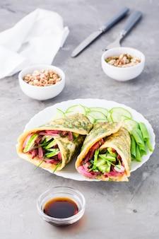 Rouleaux d'oeufs remplis de pastrami, de légumes et d'oignons verts sur une assiette, de grains germés et de sauce soja dans des bols sur la table.