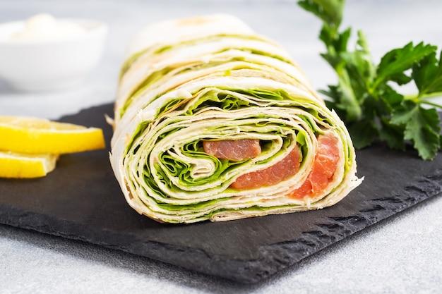 Rouleaux de pain pita fin et saumon rouge salé aux feuilles de laitue sur un support en ardoise, table en béton gris. copiez l'espace.