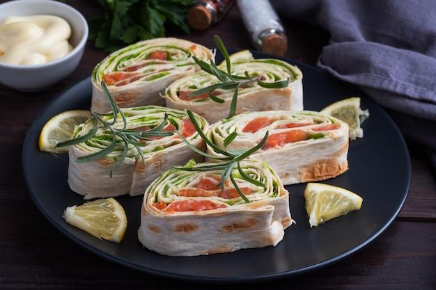 Rouleaux de pain pita fin et saumon rouge salé avec des feuilles de laitue sur une plaque en céramique noire, en bois foncé.