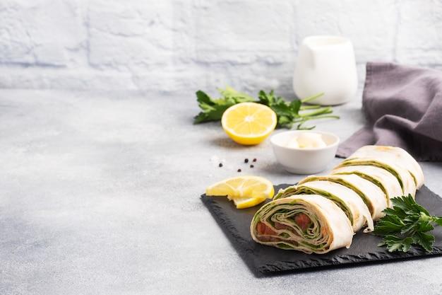 Rouleaux de pain pita fin et saumon rouge salé avec feuilles de laitue sur un support en ardoise, béton gris