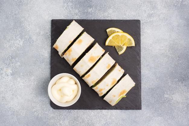 Rouleaux de pain pita fin et saumon rouge salé avec des feuilles de laitue sur un support en ardoise, fond de béton gris. copiez l'espace.