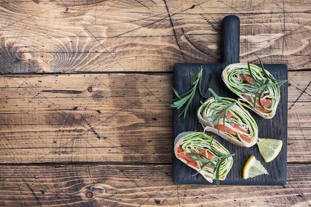 Rouleaux de pain pita mince et saumon rouge salé avec des feuilles de laitue sur une planche à découper en bois. copiez l'espace.