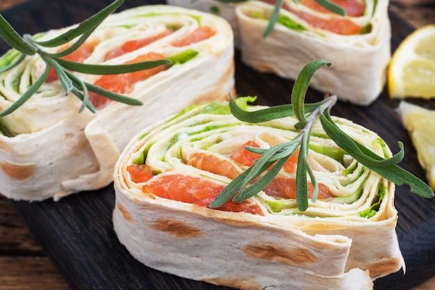 Rouleaux de pain pita mince et saumon rouge salé avec des feuilles de laitue sur une planche à découper en bois.