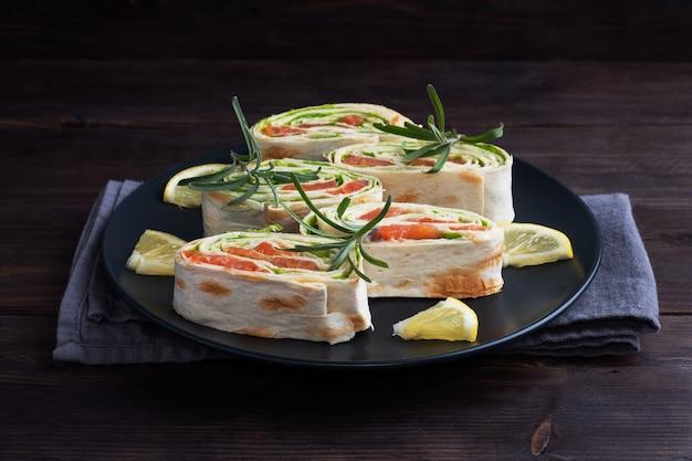 Rouleaux de pain pita mince et saumon rouge salé avec des feuilles de laitue sur une plaque en céramique noire, fond en bois foncé. copiez l'espace.
