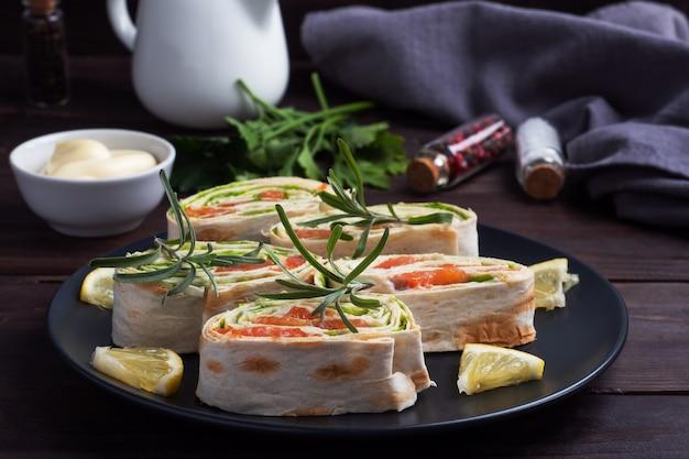 Rouleaux de pain pita mince et saumon rouge salé avec des feuilles de laitue sur une plaque en céramique noire, table en bois foncé.