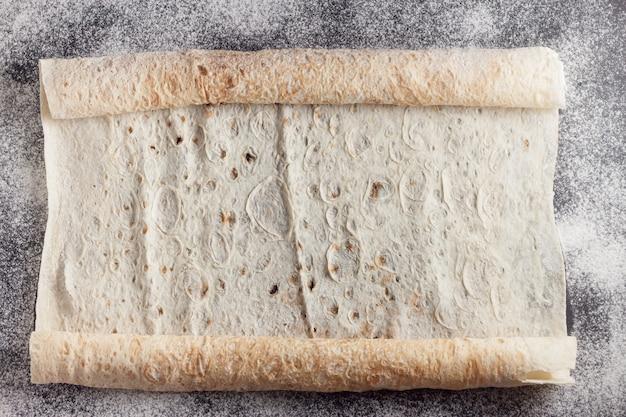 Rouleaux de pain plat frais sur une surface de cuisson.