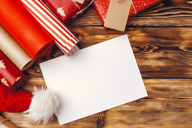 Rouleaux de papier d'emballage pour les cadeaux de noël sur planche de bois brun