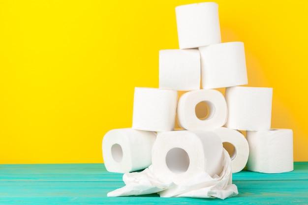 Rouleaux de papier hygiénique empilés sur du papier jaune