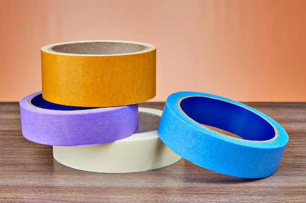 Des rouleaux de papier multicolore et de ruban adhésif en plastique se trouvent sur la table.
