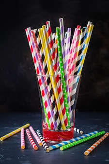 Rouleaux de papier multicolores pour cocktail ou pailles dans un bocal en verre sur fond sombre. mise au point sélective.