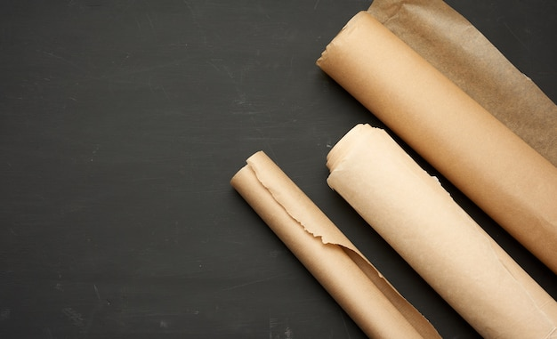 Rouleaux de papier parchemin brun sur fond de bois