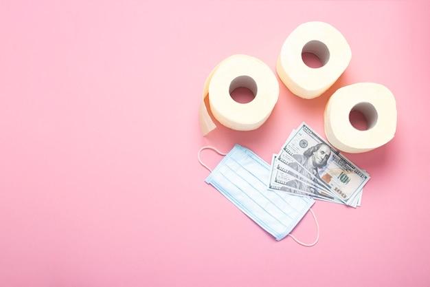 Rouleaux de papier toilette, masque médical et billets en dollars sur un rose