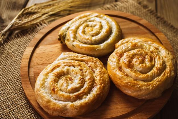 Rouleaux de pâte feuilletée copieux cuits au four avec du saumon fumé, du fromage à la crème et des herbes fraîches. fraîchement cuit.