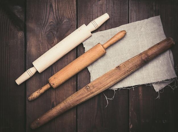 Rouleaux à pâtisserie en bois pour rouler la pâte sur fond noir, ustensiles nouveaux et très anciens, vue du dessus