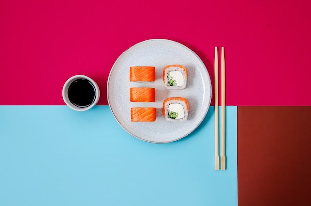 Rouleaux de philadelphie avec concombre de poisson saumon et fromage sur assiette avec sauce soja sur fond coloré concept minimal