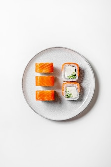 Rouleaux de philadelphie avec du poisson saumon, du concombre et du fromage sur une assiette sur fond blanc