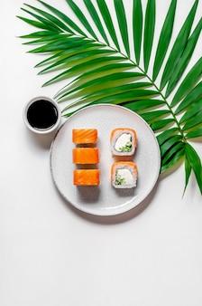 Rouleaux de philadelphie avec poisson saumon, concombre et fromage sur assiette avec sauce soja et feuille de palmier