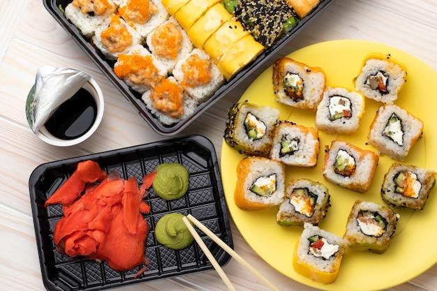 Rouleaux sur plaque jaune avec wasabi et sauce soja sur table en bois. un fruits de mer avec des baguettes.