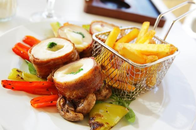 Rouleaux de poulet au fromage, légumes et pommes de terre frites
