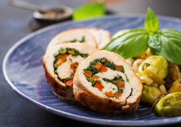 Rouleaux de poulet aux verts, garnis de choux de bruxelles cuits, pommes et poireaux sur une assiette bleue.