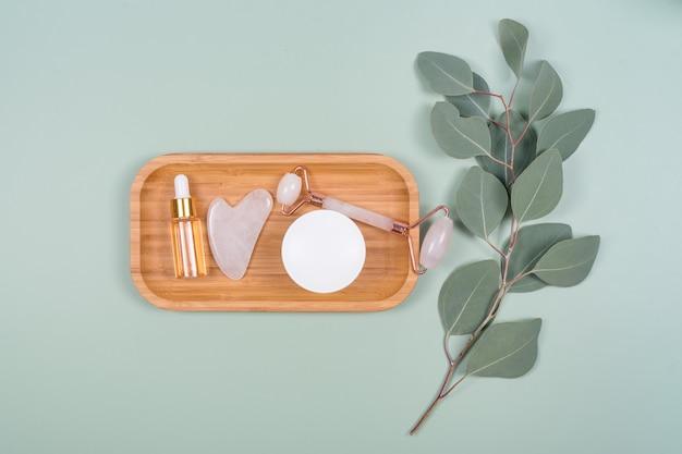 Rouleaux pour le visage, huile essentielle ou sérum cosmétique et crème cosmétique avec des feuilles d'eucalyptus naturelles sur fond vert