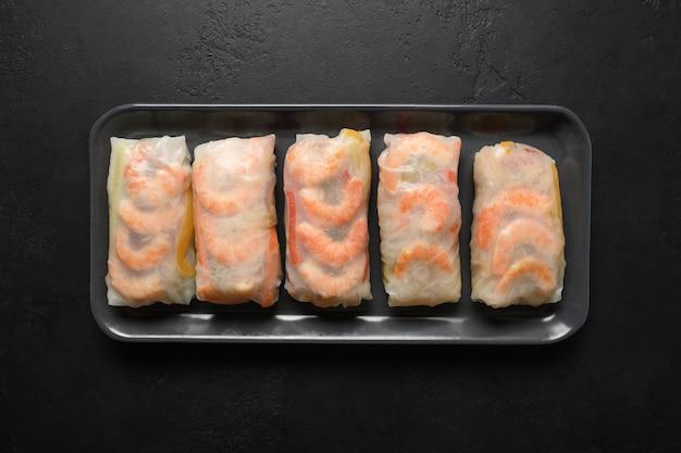 Rouleaux de printemps asiatiques aux crevettes enveloppées dans du papier de riz isolé sur un fond de pierre noire, cuisine du vietnam.