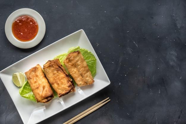 Rouleaux de printemps aux légumes frits avec ingrédients frais servis et sauce aigre dans un restaurant oriental