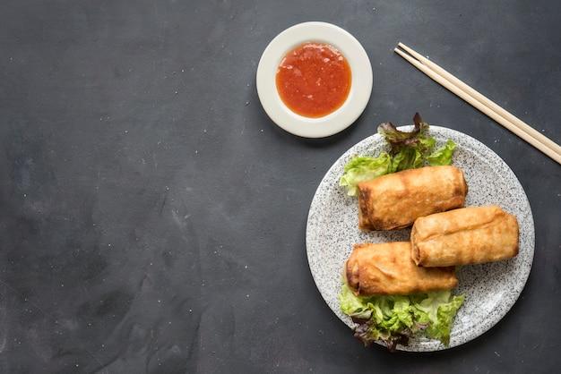 Rouleaux de printemps aux légumes frits avec des ingrédients frais servis et sauce aigre dans un restaurant oriental