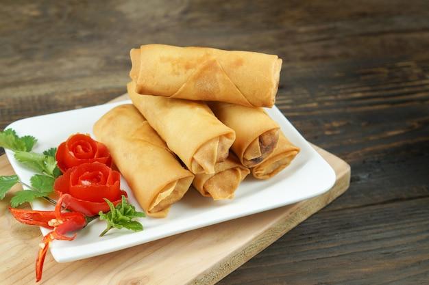 Rouleaux de printemps chinois frits servis avec une sauce chili et décorés de tomates roses à feuilles vertes sur bois, espace. concept de cuisine asiatique